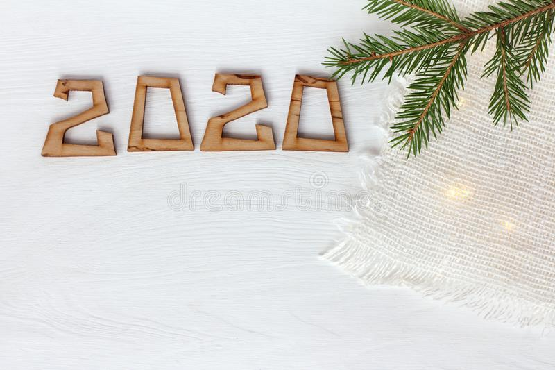 Green spruce branch and number 2020 on a wooden surface painted white top view. festive background with lights stock image