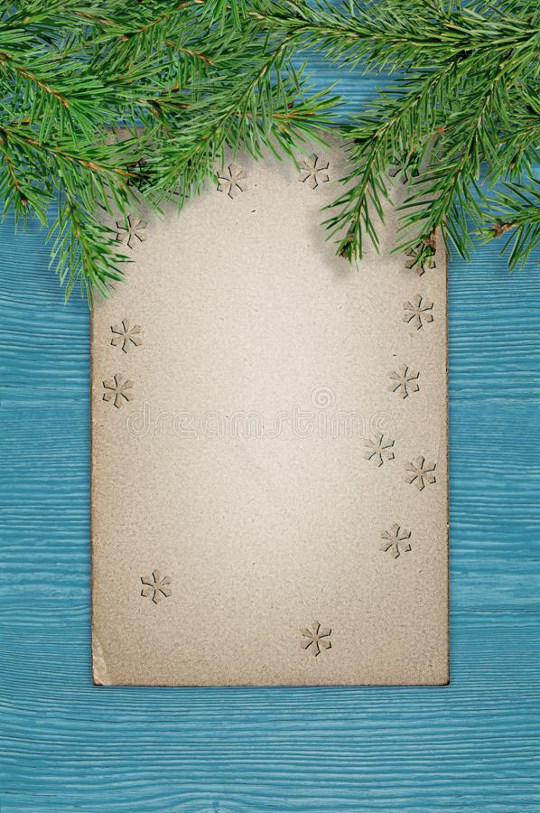 Green spruce branches and old grunge paper on a blue wood board. Christmas background royalty free stock image