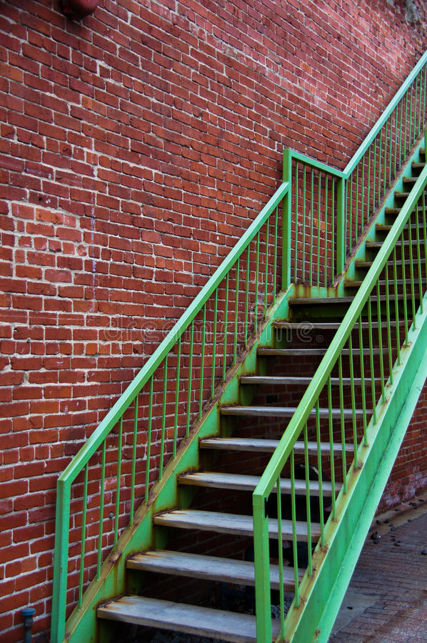 Green Staircase on Brick Wall stock photo