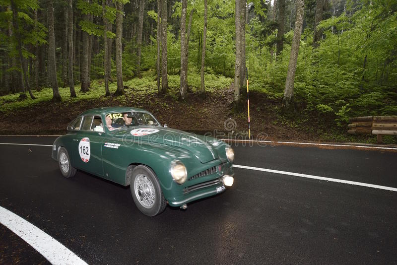 A green Stanguellini 1100 Berlinetta Bertone takes part to the 1000 Miglia classic car race. PASSO DELL'ABETONE (PT), ITALY - MAY 16: A green Stanguellini 1100 royalty free stock photos
