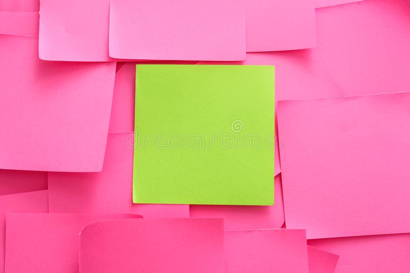 Green sticky note among pink ones. Difference and uniqueness concept royalty free stock image
