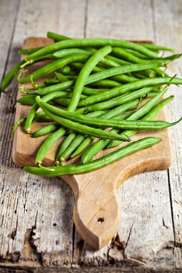 Green string beans on wooden board stock image