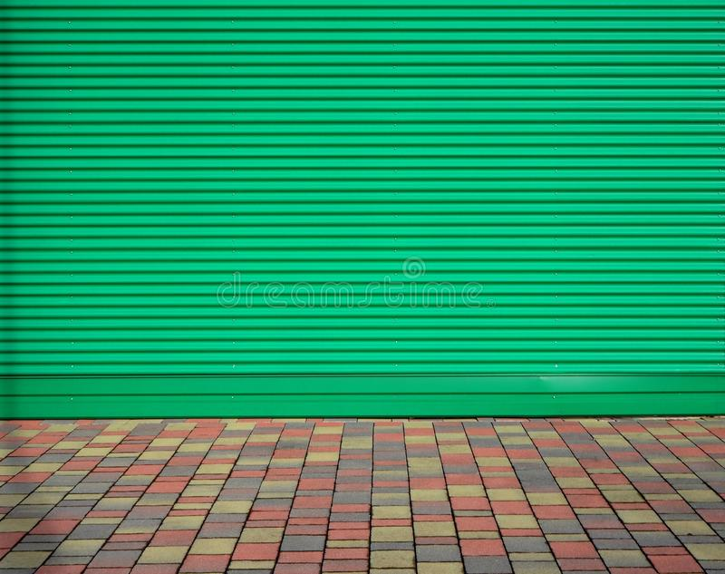Green striped aluminium cladding wall and a tiled pavement with different colors. Background and texture, copy space.  royalty free stock photography