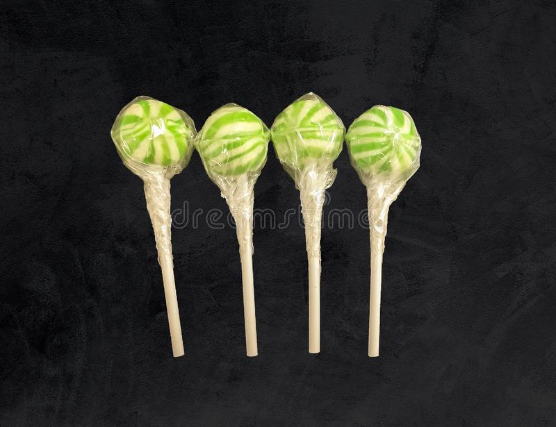 4 green striped candy lollipops in a single line stock photo