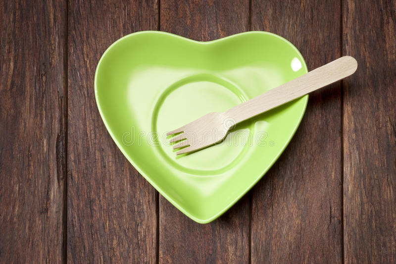 Green Heart Plate Sustainable Food. A green heart plate with a wooden fork on a wood background royalty free stock photo