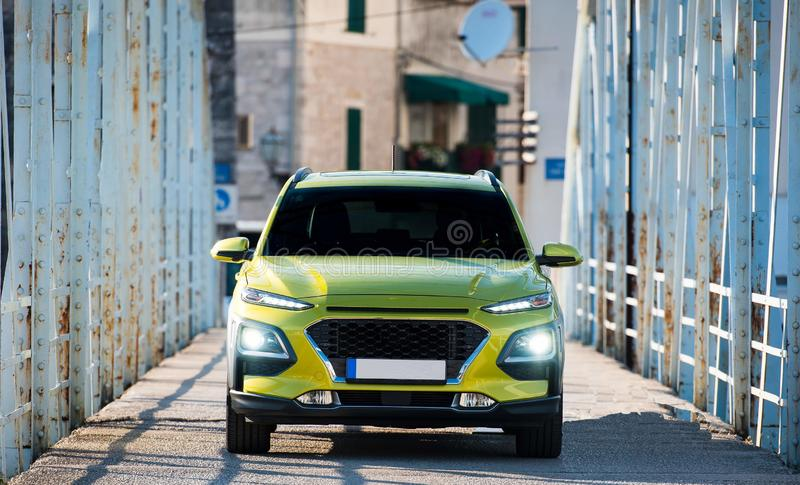 Green SUV car with lights on standing on metal bridge. Green SUV car with  front lights on standing on metal bridge royalty free stock photos