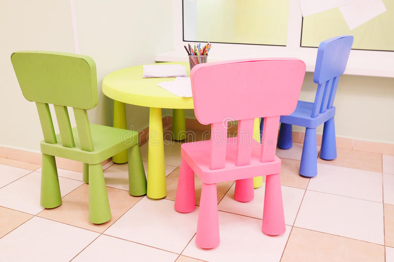Green table and colorful chairs for little kids stock photography