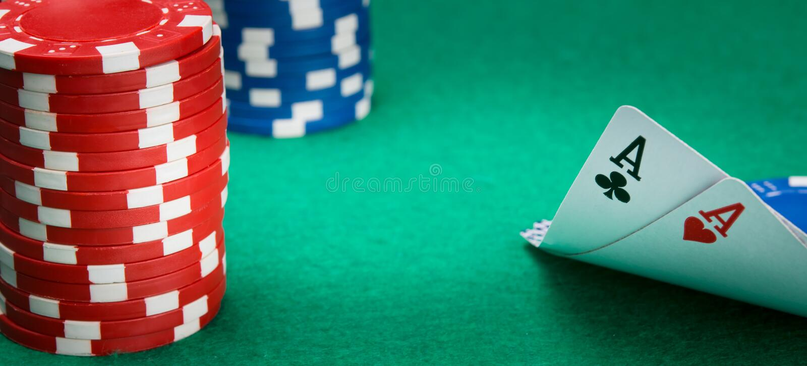 On the green table, for gambling, two ace cards are parted, on the left is a stack of chips, for playing in a casino, there is a. Place for an inscription stock photography