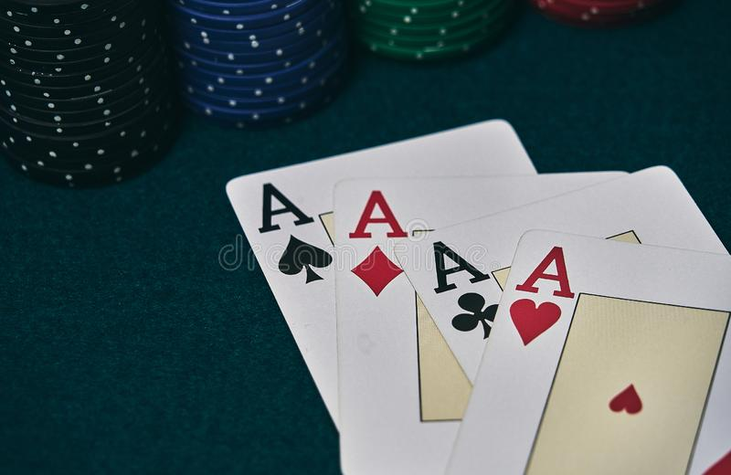 on the green table, highlights a set of four aces, in poker game next to the colored chips stock image