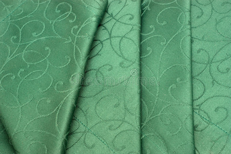 Green tablecloth and napkin. The background of textured green tablecloth and napkin closeup royalty free stock images