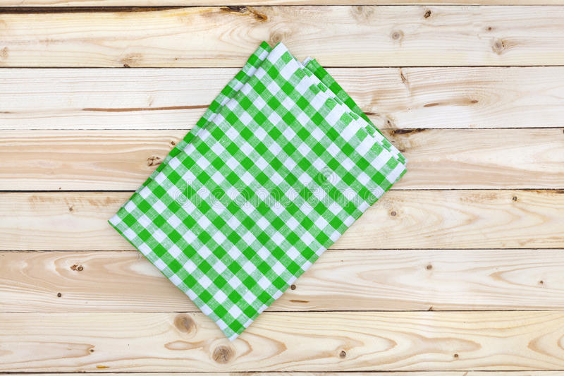 Green tablecloth on wooden table, top view. Green checkered tablecloth on a light wooden table, top view royalty free stock photos