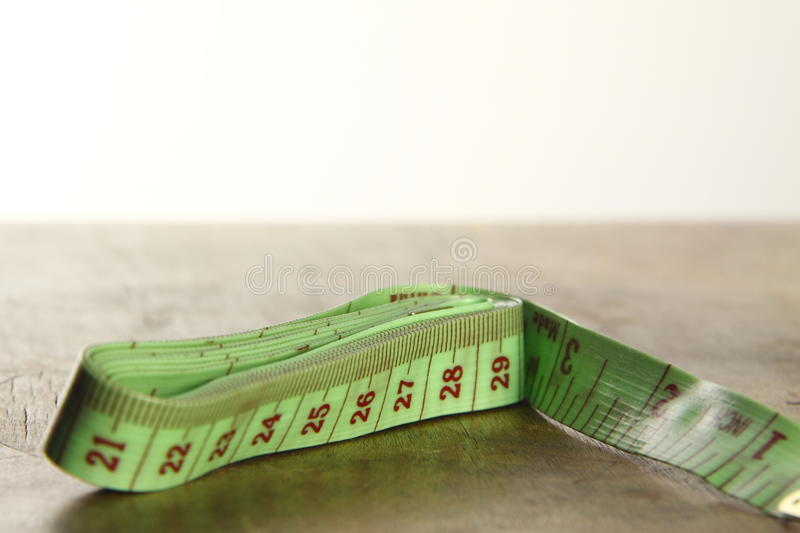 Green tapemeasure. Green tapmeasure for use in most fabric industries and weight loss royalty free stock images