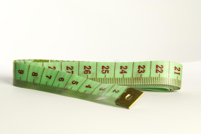 Green tapemeasure. Green tapmeasure for use in most fabric industries and weight loss stock image