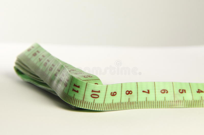 Green tapemeasure. For use in most fabric industries and weight loss royalty free stock photo