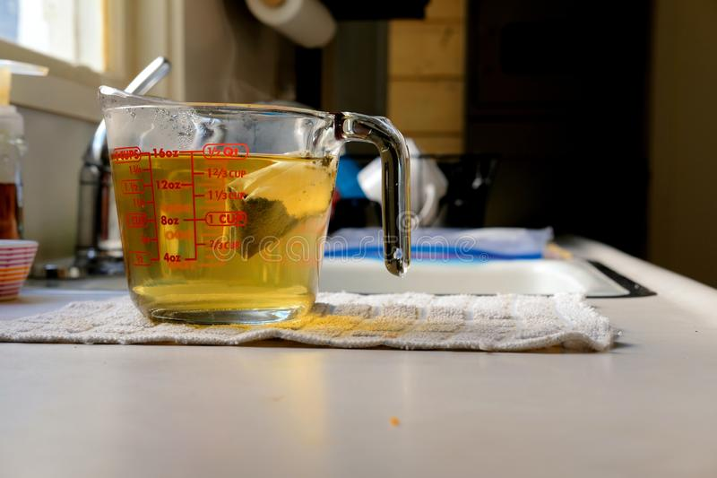 Steeping green tea bag. A green tea bag steeping in a glass measuring cup with two cups hot water on a kitchen countertop with faucet in background; an easy way stock photography