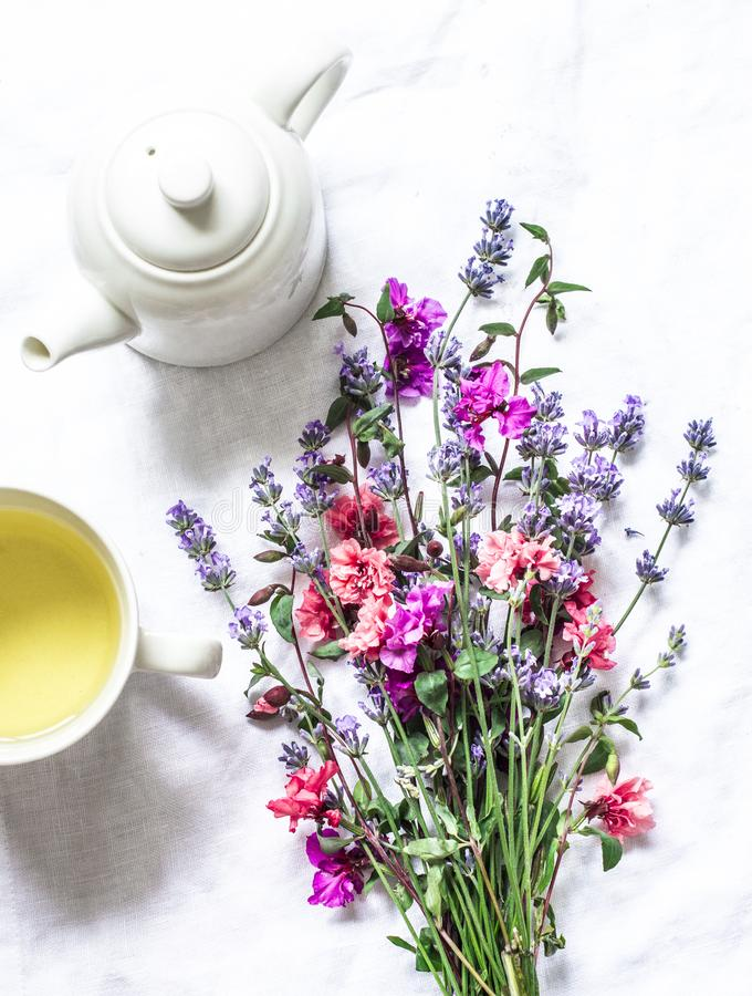 Green tea and a bouquet of garden summer flowers on a light background, top view. Flat lay royalty free stock photography