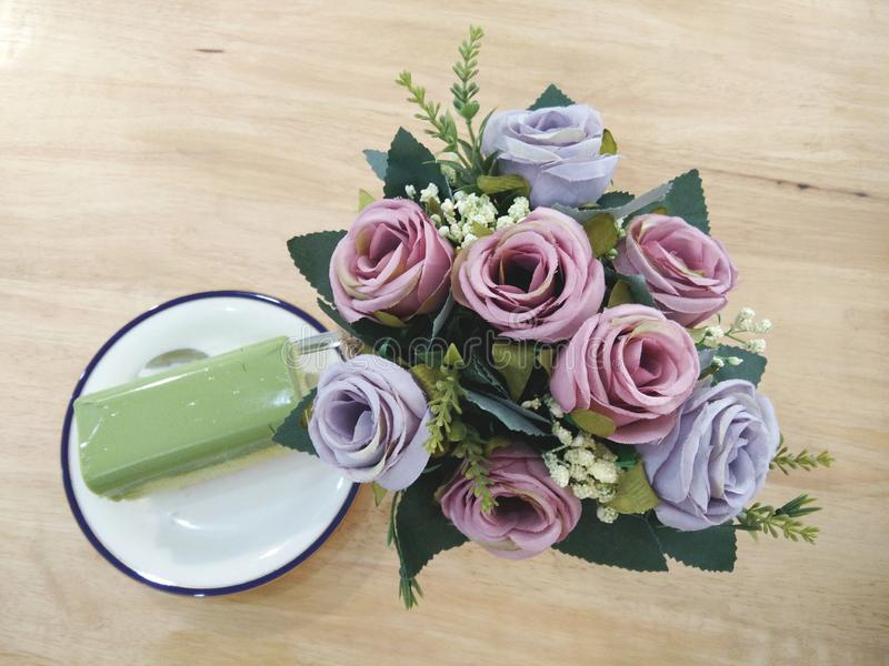 Green tea cake on white dish, fake blossom rose flowers bouquet on table. Rectangle green tea cake on white dish, fake blossom rose flowers bouquet on wooden royalty free stock images