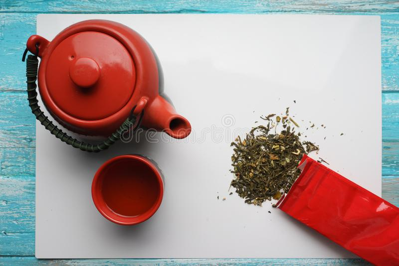 Green tea, close-up, top view Dry leaves, teapot, a Cup of tea, and red packing bag on white background royalty free illustration