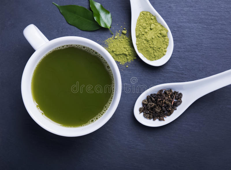 Green tea in a cup on the black background royalty free stock images