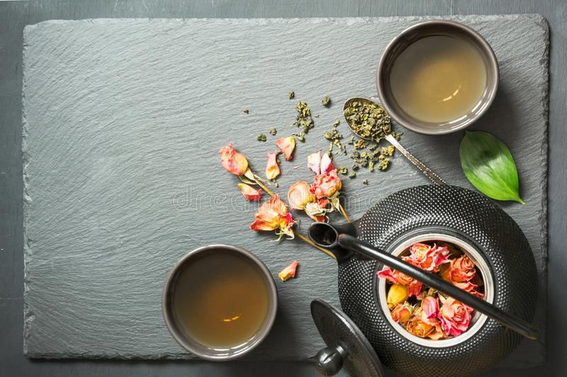 Green tea with rose flower on black slate background. Top view with copy space. stock photography