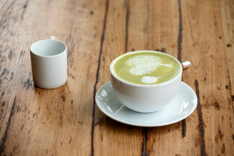 Green tea or hot matcha latte in white ceramic cup with saucer placing together with syrub. Cup on retro wooden table stock photography