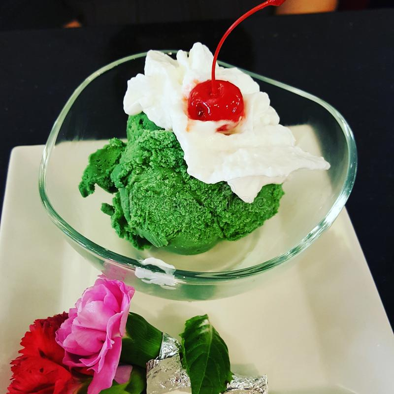 Green Tea Ice Cream. Made fresh and sweet at Thai Restaurant. With elegant roses to conpliment the dish and cherry on top stock images