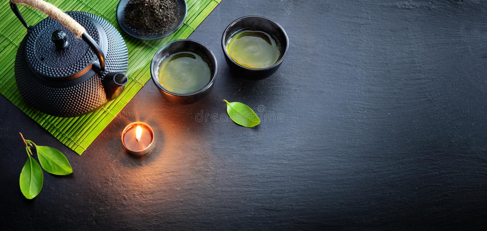Green Tea In Iron Asian Teapot With Leaves And Bamboo Mat. On Black Stone royalty free stock photos