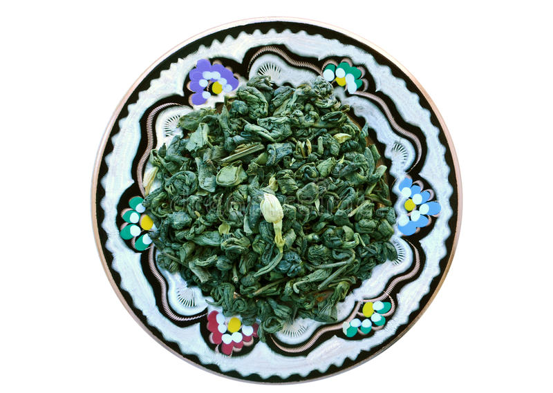 Green tea with jasmin on the round plate. Green tea with jasmin on the round cupreous fancy plate ,white background stock image