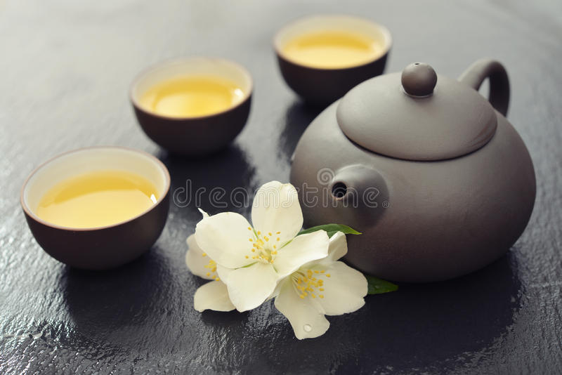 Green tea with jasmine. Green tea in cups with jasmine flowers and teapot on wet graphite background royalty free stock images