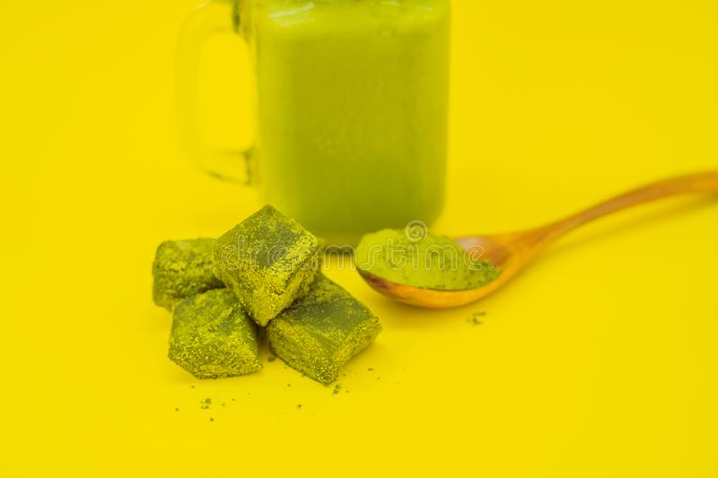 Green tea latte with ice in mason jar and straw and spoon with powder matcha and candy made of matcha on yellow stock photo