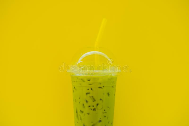 Green tea latte with ice in plastic cup and straw in female hand with yellow manicure on yellow background. Homemade royalty free stock images