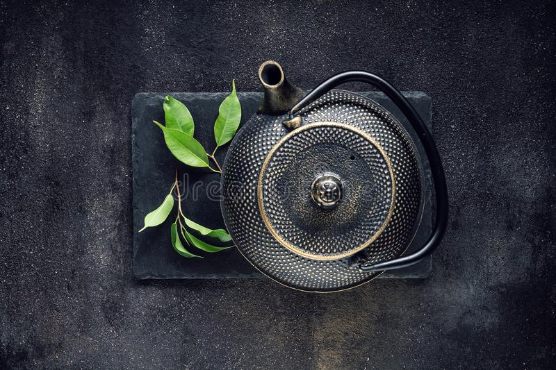 Green tea leaf with black teapot royalty free stock images