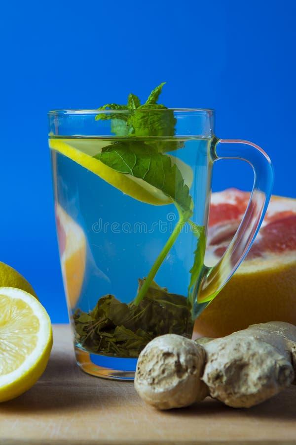 Green tea with lemon, ginger, grapefruit, mint. Blue background stock image