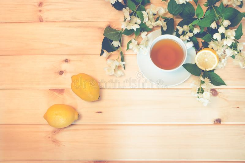 Green tea, lemon and jasmine flowers on wooden background. stock photography
