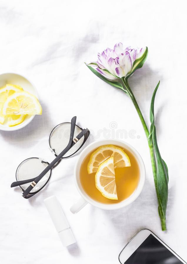 Green tea with lemon, tulip flower, headphones, smartphone - free relax time still life on a white background, top view stock photos