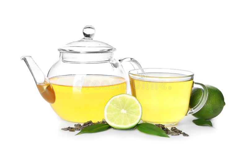 Green tea with lime in glass cup and pot on white background stock photography