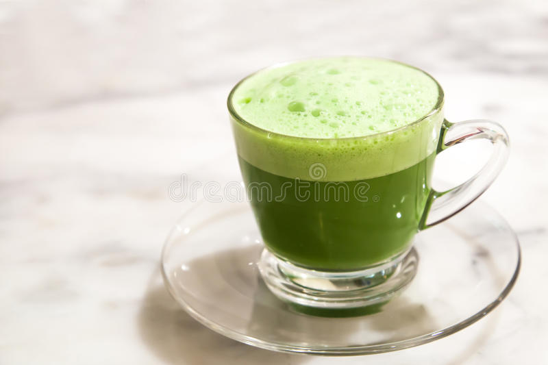 Green tea milk cup in glass put on the stone table. royalty free stock photos