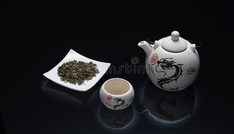 Green tea with white tea set and dragon drawing. Gree tea with cup and white teapot on a bright black background in which the drawing of a dragon is reflected royalty free stock images