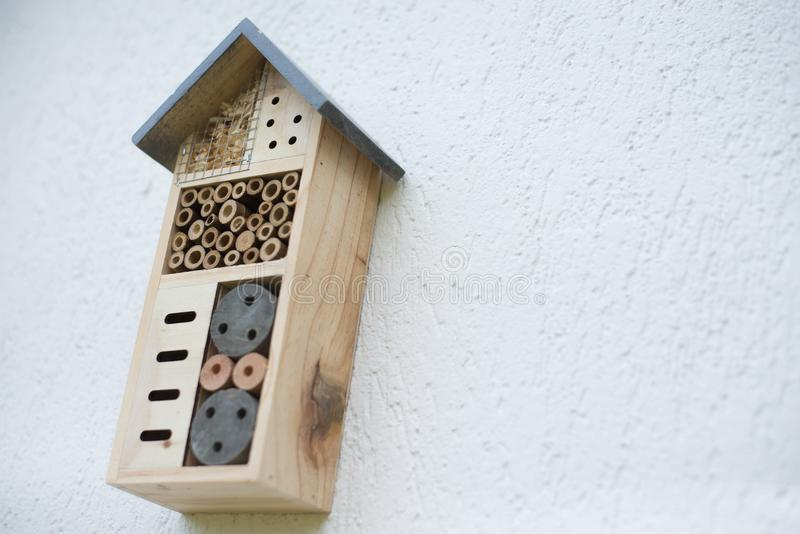 Insect hotel installed on house wall stock image