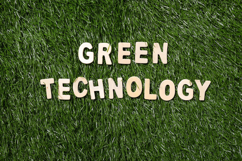 Green Technology Wooden Sign On Grass. Green technology wooden sign on green grass background stock images