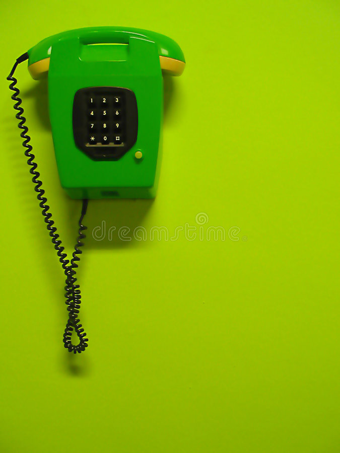 Green telephone. Hanging on a green wall