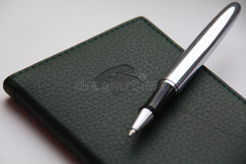 Green telephone notebook and ball-poin. Green notebook with stamping sign of the telephone and ball-point pen royalty free stock photos