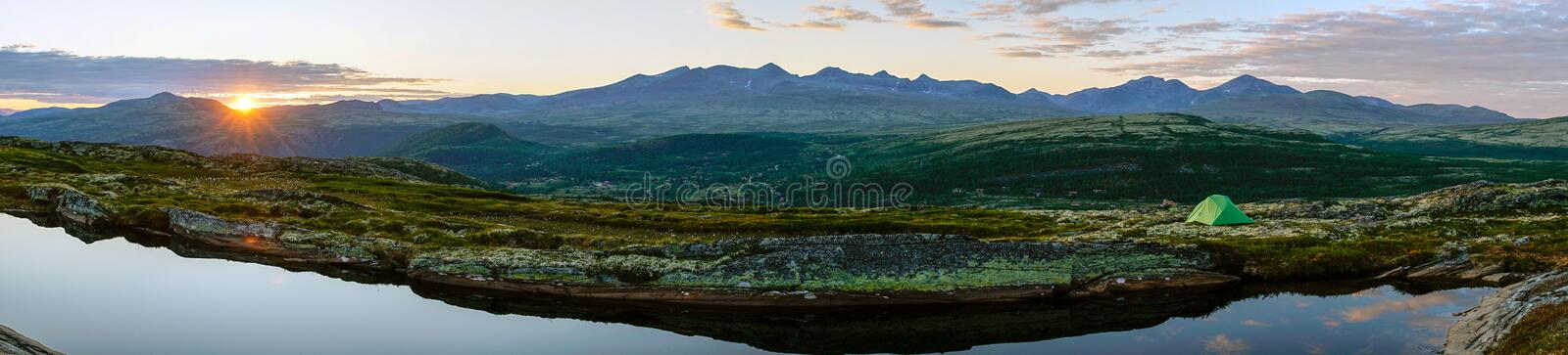 Green tent outdoors in the mountains by lake during sunset hours. Sunset/sunburst and clouds in the background, big panorama. Mountain scenery. Wilderness and royalty free stock images