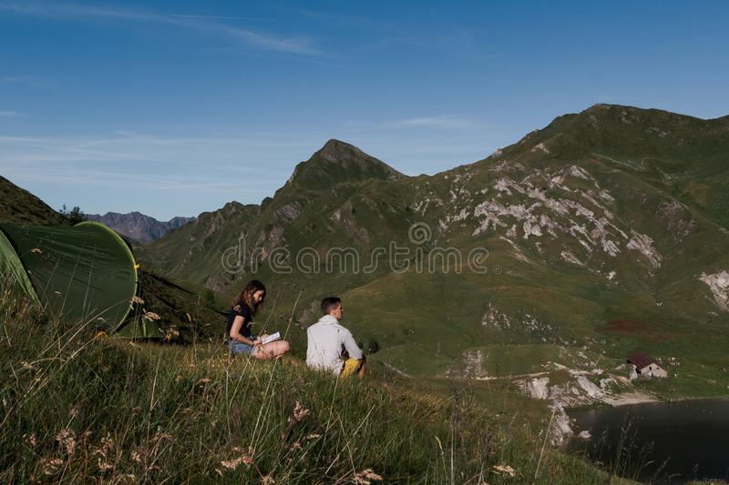 Green tent placed in a peaceful down in the mountains of switzerland. Girl reading a book, boy admires the view stock photo