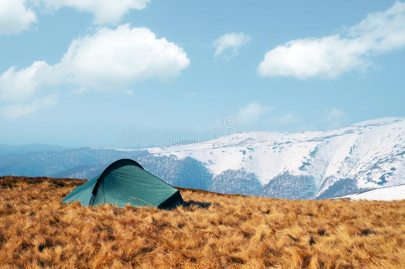 Green tent in spring mountains. Green tent on amazing meadow in spring mountains. Landscape photography, travel concept stock photo