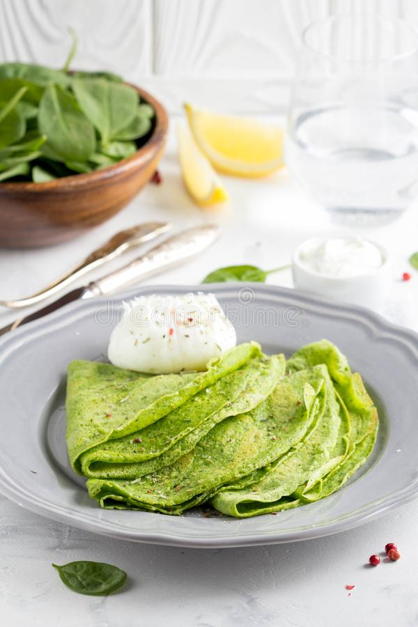 Green thin pancakes with spinach, poached egg, sour cream, lemon royalty free stock image