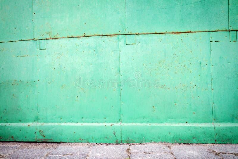 Green tin wall. Old green weathered metal tin street wall royalty free stock photos