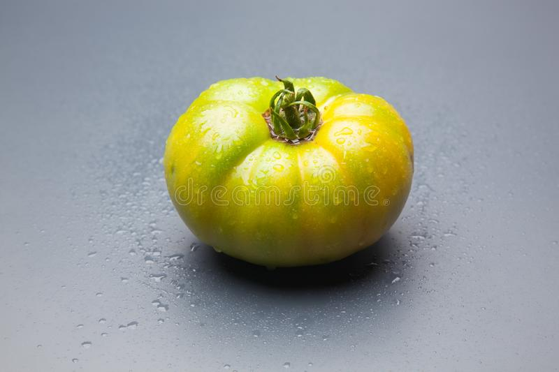 Green tomato on plain background, healthy food. Green tomato, waiting to be matured artificially, on a plain background, healthy food, tomato that is still to royalty free stock photos
