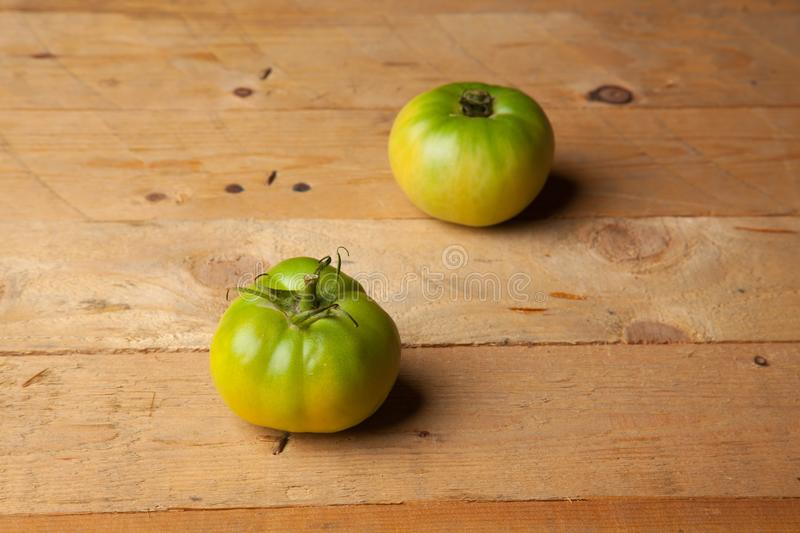 Green tomatoes on plain background. Organic tomatoes, grown without chemicals or pesticides, green tomatoes on a plain background. There are people who like to stock image