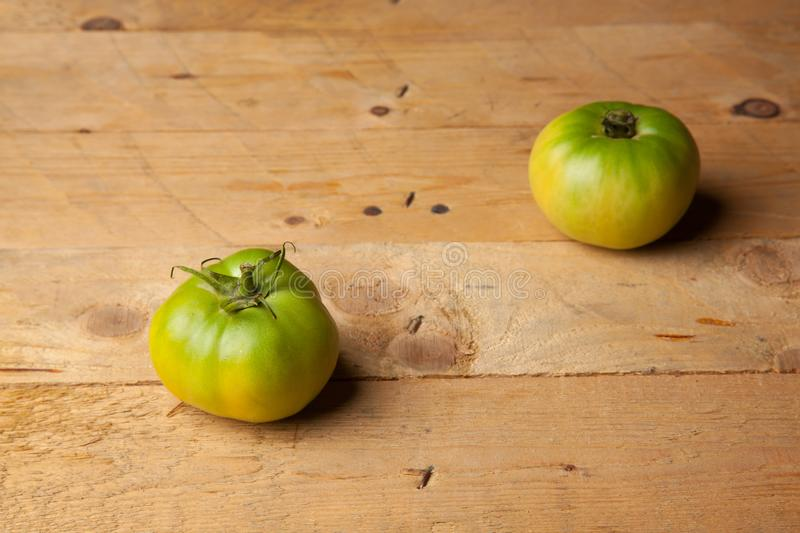 Green tomatoes on plain background. Organic tomatoes, grown without chemicals or pesticides, green tomatoes on a plain background. There are people who like to stock photography